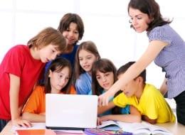 Teacher instructing elementary schoolchildren on using the laptop computer